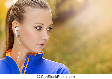 Sporty woman runner listens to music in nature - Sporty and...