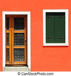 front door in vivid orange painted house in Burano village,...