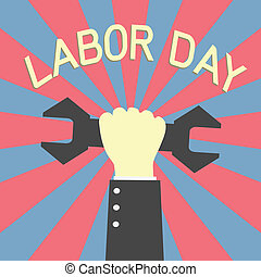 labor day - hand holding up wrench in labor day concept