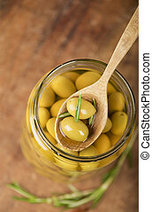 Close up green olives in bank, rosemary on a wooden...