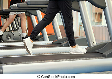 People at the gym exercising. Run on a machine.
