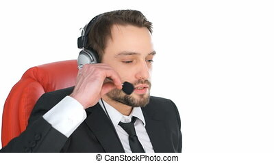 Businessman wearing a headset concentrating as he listens to...