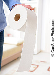 Hand holding toilet paper at home