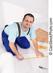 Man laying laminate floor at home