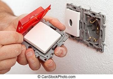 Electrician hand changing or installing an electrical switch...