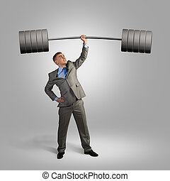success in business - businessman holding a barbell with one...