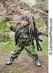 Yong hunter boy with the rifle is posing on the forest...