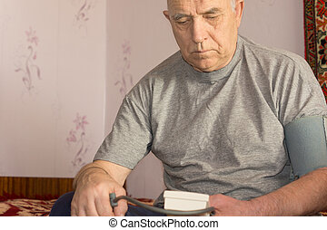 Elderly man taking his blood pressure