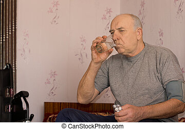 Elderly man taking his medication drinking the tablets down...