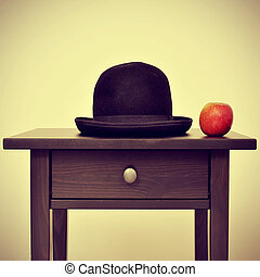 picture of a bowler hat and an apple on a bureau, homage to...