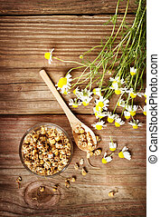 Dried chamomile tea with fresh chamomile flowers on rustic...