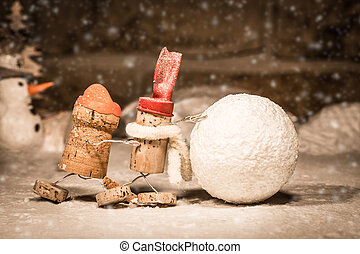 Wine cork figures, Concept two men rolling a snowball -...