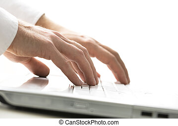 Man typing on a laptop computer - Closeup view of the hands...