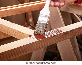 Painting wooden rack - applying protective primer on wooden...