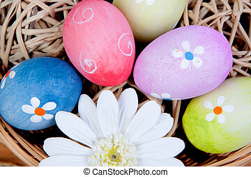 Easter eggs decorated with daisies tucked in a basket on a...