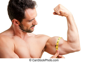 Measuring His Bicep - Fit man measures his bicep with a...