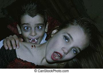 halloween - costumed children playing vampires on halloween