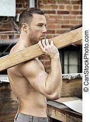 Hunky guy with lumber - Sexy macho guy shirtless holding...