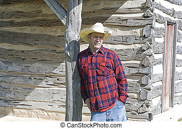 Cowboy Leaning on a Wooden Post - Handsome rugged cowboy...