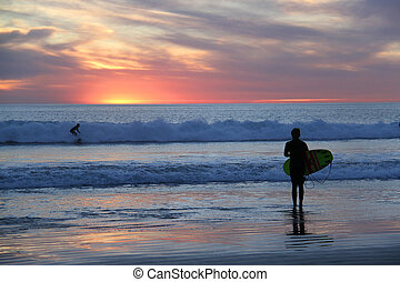 surfgirl if front of beautiful sunset