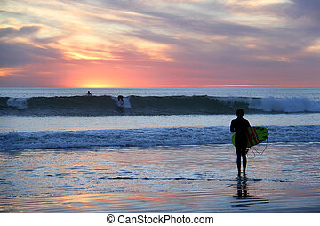 surfgirl if front of wonderful sunset