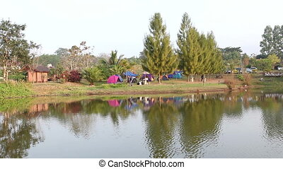 Group of people enjoy tent camp beside natural lake
