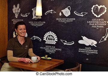 Frau bei einer Tasse Kaffee - junge Frau entspannt sich bei...