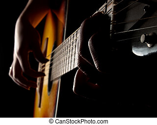 Guitar blues - Female hands playing acoustic guitar on black...