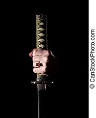 Power - Japanese katana sword in man\'s hand in darkness