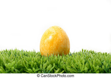 yellow easter egg on grass - a yellow easter egg on grass