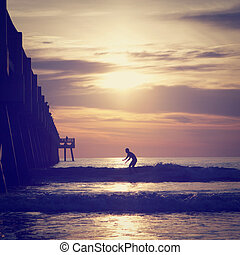 Surfing - Silhouette of a surfer in Florida with retro...