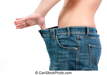 loosing weight - slim woman trying on her big jeans