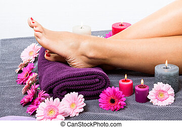 Bare feet of a woman surrounded by flowers - Overhead view...
