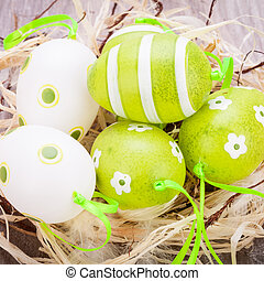 Colourful green Easter eggs in straw - Collection of four...