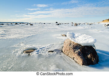Stones in the ice on the Baltic Sea coast