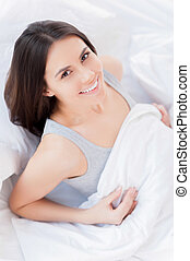 Waking up with smile Top view of beautiful young woman lying...
