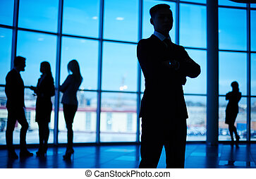 Business leader - Outlines of business team standing against...