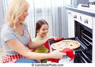Mother and daughter cooking - Portrait of happy young woman...