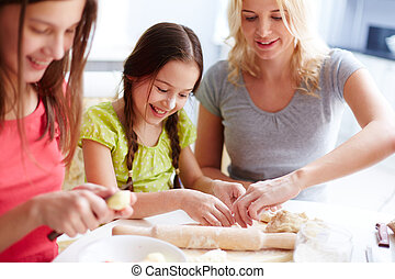 Cooking pastry - Portrait of happy girls and their mother...