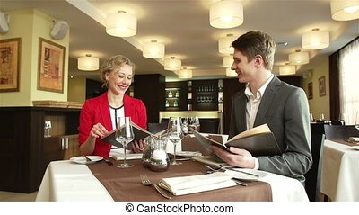 Restaurant Date - Cheerful young couple looking through menu...
