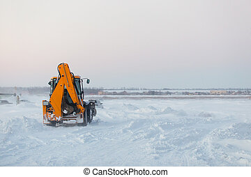 Tractor with snow plow at work during a winter storm