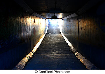 Light at End of Tunnel - Dark pedestrian tunnel with...