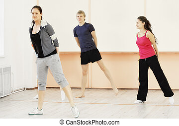 Four people in gym making exercises