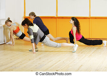 Four people making stretching exercises in gym