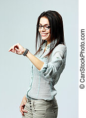 Young smiling businesswoman looking at her watch on wrist on...