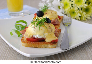 Eggs Benedict with ham and tomato on toast with cheese and...