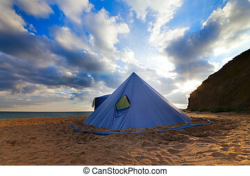 Conical tent on summer beach and blue sky with clouds.Wide...