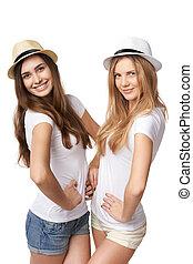 Two women friends having fun Two happy girls in straw hats...