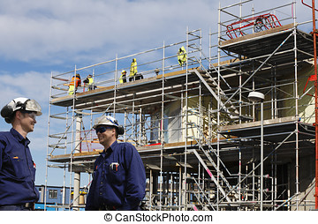 construction industry and workers - two site workers inside...