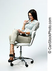 Young beautiful woman sitting on the chair and using table...